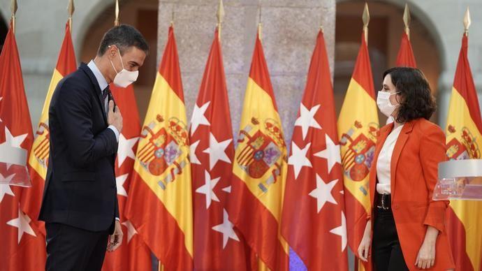 Pedro Sánchez e Isabel Díaz Ayuso entre banderas.