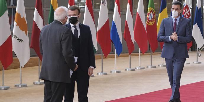 Macron y Borrell hablan mientras Pedro Sánchez se acerca a ellos.