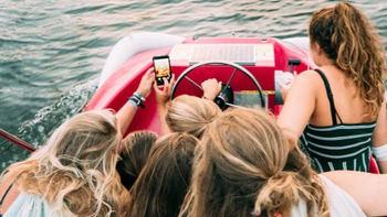 Jjóvenes en una embarcación de recreo con el móvil.